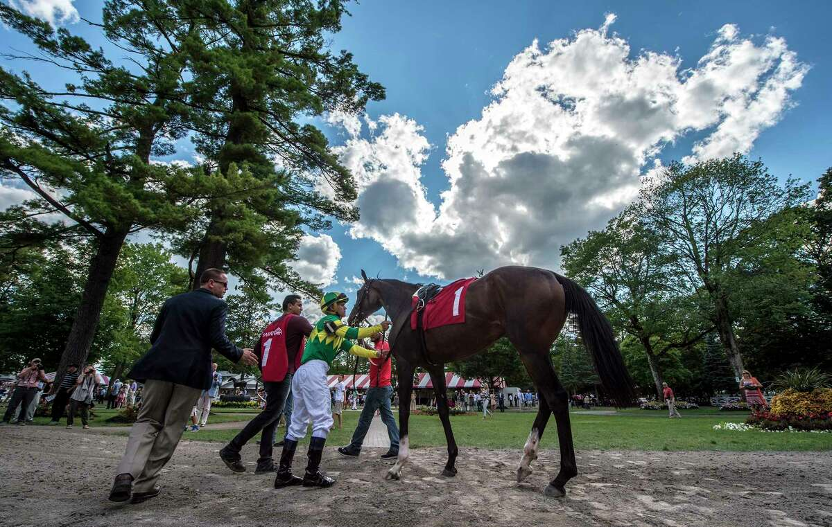 Jockey Javier Castellano prepares to jump up on Galileo's Song with an assist from trainer Chad Brown for the 7th race on the card with beautiful clouds above at the Saratoga Race Course Sunday Aug. 13, 2017 in Saratoga Springs, N.Y. (Skip Dickstein/Times Union)