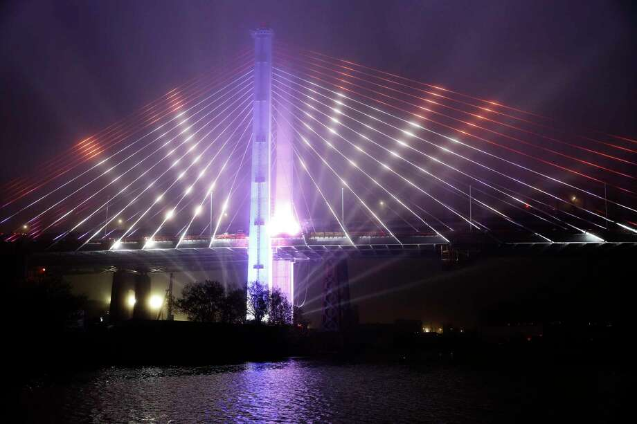 """FILE - In this April 27, 2017, file photo, a performance of the """"New York Harbor of Lights"""" is featured at the grand opening of the new Kosciuszko Bridge span connecting Brooklyn and Queens, in New York. Gov. Andrew Cuomo liked the idea of stringing New York City's bridges with high-tech lights that change color and pulsate to the beats of Broadway showtunes. But the plan, meant to delight tourists and residents alike, is sputtering amid criticism that the money for the lights should have gone to the city's beleagured subway system. (AP Photo/Kathy Willens, File) ORG XMIT: NYR202 Photo: Kathy Willens / Copyright 2017 The Associated Press. All rights reserved."""