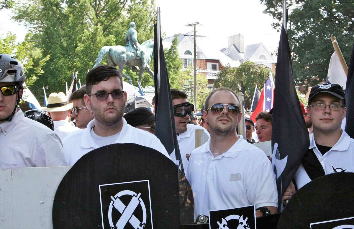 In this Saturday, Aug. 12, 2017 photo, James Alex Fields Jr., second from left, holds a black shield in Charlottesville, Va., where a white supremacist rally took place. Fields was later charged with second-degree murder and other counts after authorities say he plowed a car into a crowd of people protesting the white nationalist rally. (Alan Goffinski via AP) ORG XMIT: AX601