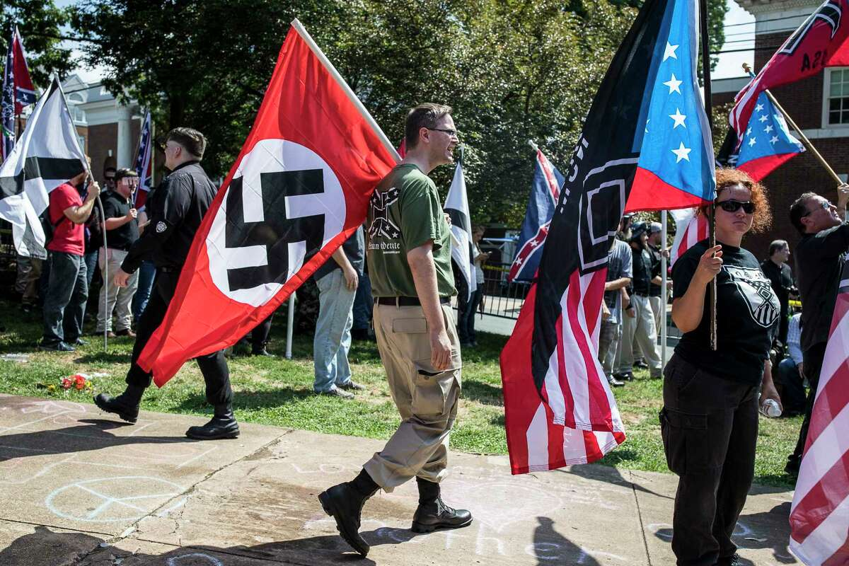 A white nationalist carries the Nazi flag during a OUnite the RightO rally in Charlottesville, Va., Aug. 12, 2017. After the rally descended into scenes of intense violence and was subsequently dispersed, a car plowed into a crowd of counterprotesters, killing at least one person and injuring at least 19 others. (Edu Bayer/The New York Times) ORG XMIT: XNYT140