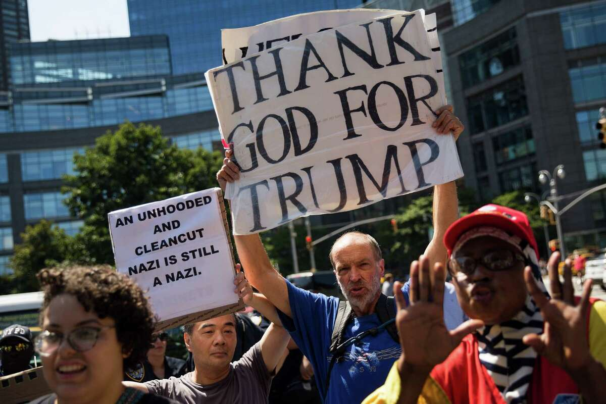 NEW YORK, NY - AUGUST 13: A counter-protestor and supporter of President Donald Trump (2nd from R) makes his voice heard during a protest against white supremacy and racism in Columbus Circle, August 13, 2017 in New York City. The rally was organized by a New York City based group called 'Refuse Fascism' following clashes between white supremacists and counter-protestors in Charlottesville, Virginia on Saturday, August 12th. Heather Heyer, 32, was killed in Charlottesville when a car driven by a white supremacist barreled into a crowd of counter-protesters following violence at the 'Unite the Right' rally. (Photo by Drew Angerer/Getty Images) ORG XMIT: 775022759