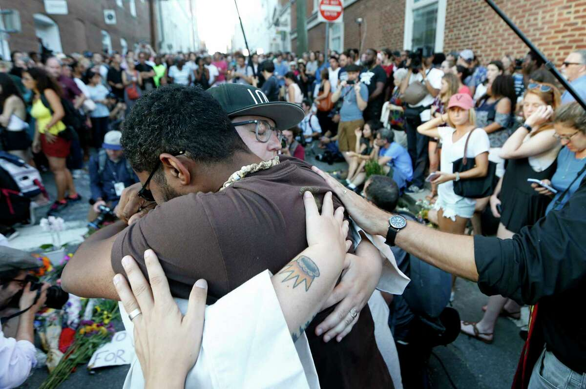 Brittany Caine-Conley, an organizer for Congregate Charlottesville, is embraced after addressing the crowd at a vigil Sunday.