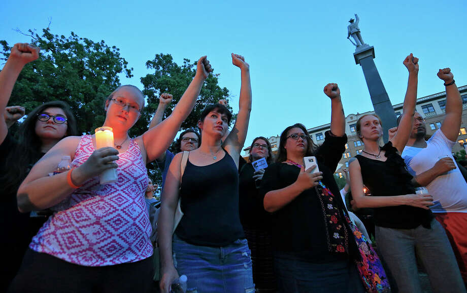 People attend a candle light vigil, Sunday Aug. 13, 2017 at Travis Park, for the victims in Charlottesville, Va. A monument and statue of a Confederate soldier (background) was the subject of a rally that brought about 500 hundred protesters to the park the day prior.Click through the slideshow to view some places in Texas where remnants of the Confederacy are alive and well. Photo: Edward A. Ornelas, San Antonio Express-News / © 2017 San Antonio Express-News