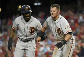San Francisco Giants' Denard Span, left, helps Joe Panik, right, after Panik was out at home by Washington Nationals catcher Matt Wieters during the fourth inning of the second baseball game of a split doubleheader, Sunday, Aug. 13, 2017, in Washington. (AP Photo/Nick Wass)