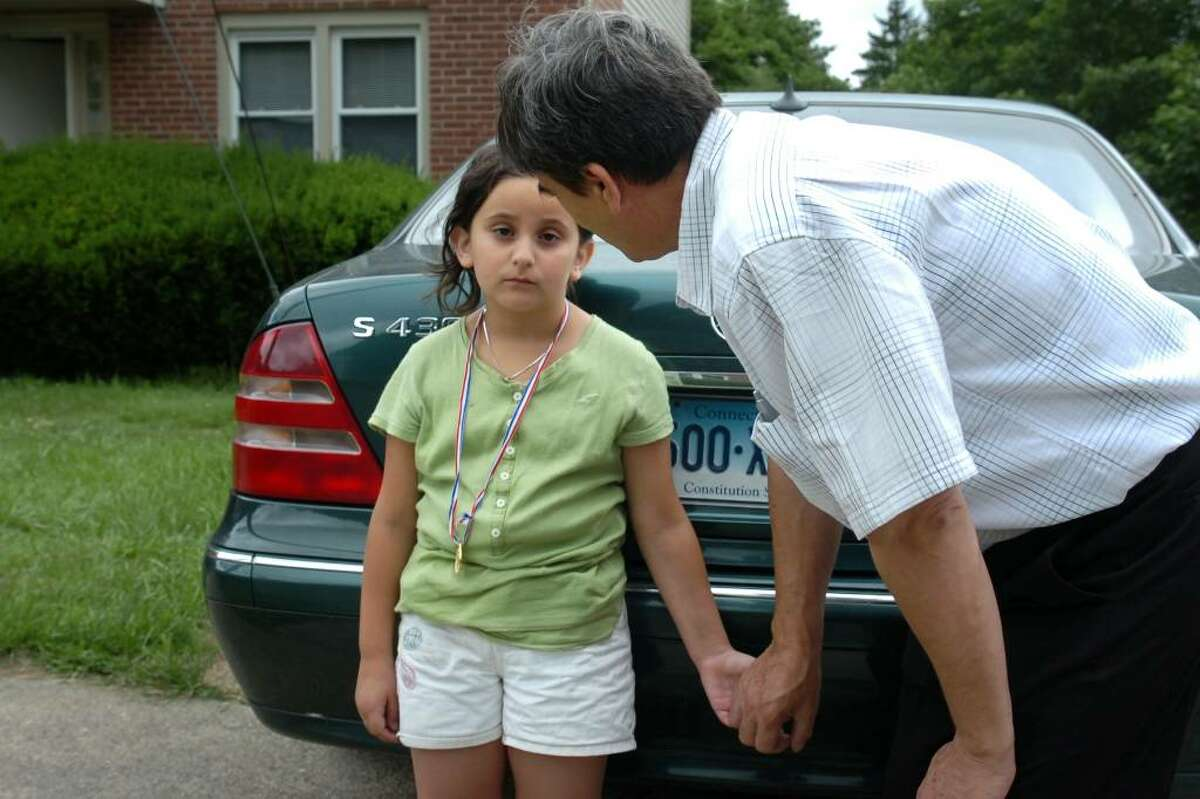 Aferdita Emini, 6, is greeted by her uncle, Skender Emini, after returning home from school in Naugatuck, Conn. Thursday, June 17th, 2010. Aferdita and her three siblings will leave for Serbia with their uncle on Saturday.