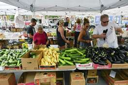 Visitors to a farmers market on Bedford Street pick up fresh fruits, vegetables and breads on Saturday, August 12, 2017  in Stamford, Connecticut.