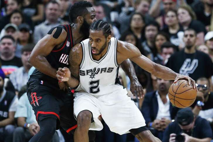 Spurs forward Kawhi Leonard (2) looks to drive past Houston Rockets guard James Harden (13) during the first half of Game 2 of the second round of the Western Conference playoffs at the AT&T Center on May 3, 2017, in San Antonio.