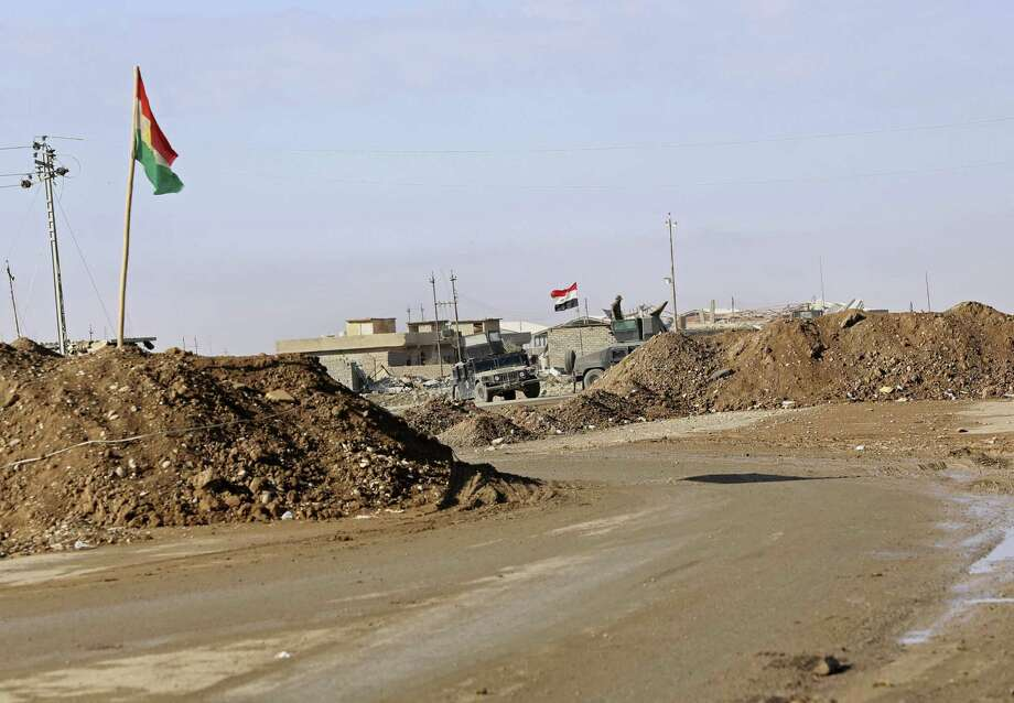 In this Saturday, Dec. 3, 2016 photo, military vehicles guard an Iraqi Army checkpoint flying an Iraqi flag, center, next to a Kurdish checkpoint with a Kurdish flag, outside Irbil, northern Iraq. The sand berms and trenches snake across northern Iraq all the way to Syria, alongside newly paved roads and sprawling checkpoints decked with Kurdish flags, in what increasingly resembles an international border. The boundary takes in lands claimed by the Kurds and the Baghdad government, and could ignite a new conflict once the Islamic State group is defeated. (AP Photo/Hadi Mizban) Photo: Hadi Mizban, STF / Associated Press / Copyright 2016 The Associated Press. All rights reserved.