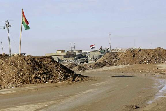 In this Saturday, Dec. 3, 2016 photo, military vehicles guard an Iraqi Army checkpoint flying an Iraqi flag, center, next to a Kurdish checkpoint with a Kurdish flag, outside Irbil, northern Iraq. The sand berms and trenches snake across northern Iraq all the way to Syria, alongside newly paved roads and sprawling checkpoints decked with Kurdish flags, in what increasingly resembles an international border. The boundary takes in lands claimed by the Kurds and the Baghdad government, and could ignite a new conflict once the Islamic State group is defeated. (AP Photo/Hadi Mizban)