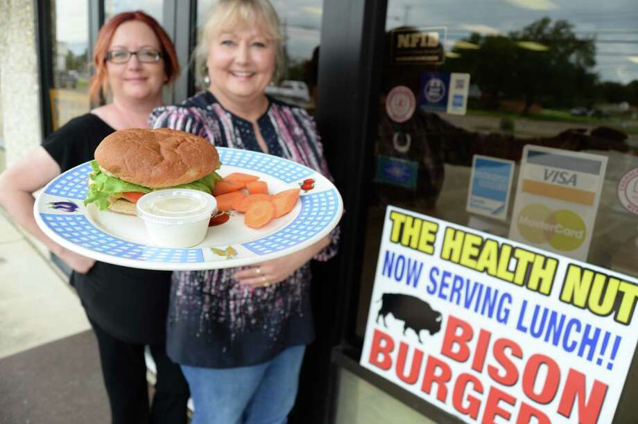 Karen Guidry, owner of The Health Nut in Deer Park, says the restaurant's burger with buffalo meat is a customer favorite. Assistant manager Shelley Stokes is behind her.