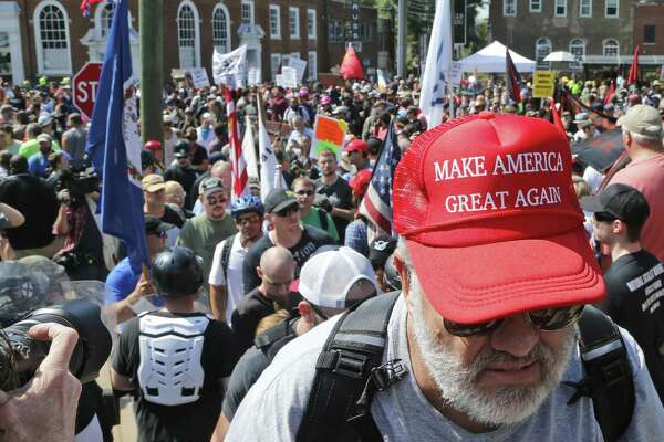 A white nationalist demonstrator walks into Lee Park in Charlottesville, Va., Saturday. Hundreds of people chanted, threw punches, hurled water bottles and unleashed chemical sprays on each other after violence erupted at a white nationalist rally in Virginia. Three people lost their lives.