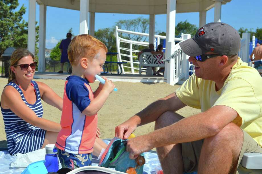 Aaron and Chrissy Parrish of Darien share a moment with their son, James, 19 months, at Weed Beach, Sunday. Photo: Jarret Liotta / For Hearst Connecticut Media / Darien News Freelance