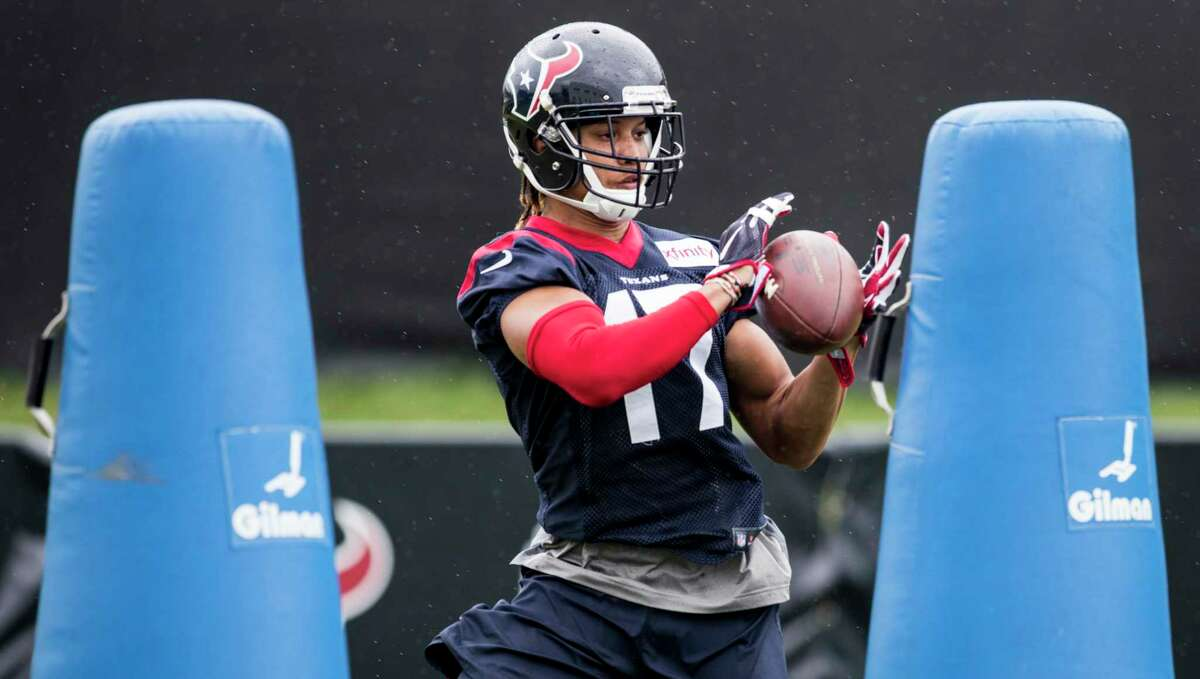 Houston Texans wide receiver Dres Anderson makes a catch while running a drill around tackling dummies during training camp at The Greenbrier on Monday, Aug. 14, 2017, in White Sulphur Springs, W.Va.