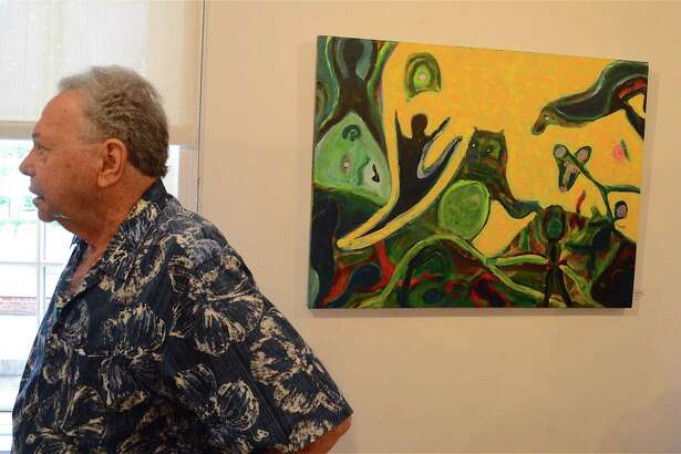 "Fairfield artist Al Coyote Weiner stands by his painting ""Dali's Dancers"" at the ""Bending Reality"" opening reception at the Bruce A. Kerschner Gallery in the Fairfield Public Library, Saturday, Aug. 12, 2017, in Fairfield, Conn."