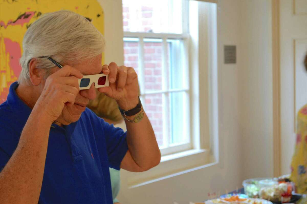 Arthur Egol of Stamford dons 3D glasses to view a work at the