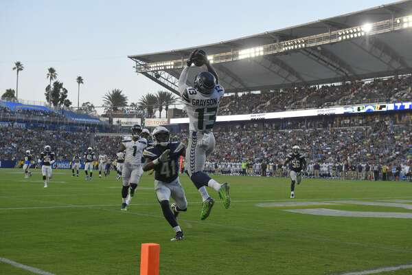 Seattle Seahawks wide receiver Cyril Grayson (13) makes a catch before entering the end zone as Los Angeles Chargers cornerback Randall Evans (41) defends during the second half of an NFL preseason football game Sunday, Aug. 13, 2017, in Carson, Calif. Originally called a touchdown, the play was reversed upon review. (AP Photo/Mark J. Terrill)