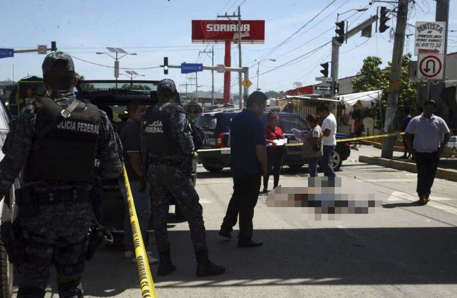 WARNING: Graphic images. The following photos contain content that some viewers may find disturbing.Federal police tape off the area where a man who was shot dead in broad daylight on a central avenue in Acapulco, Mexico, Sunday, Aug. 13, 2017. At least four people were shot dead in Acapulco Sunday, as Mexico recently recorded its highest monthly murder total in at least 20 years. Photo: Bernandino Hernandez/AP