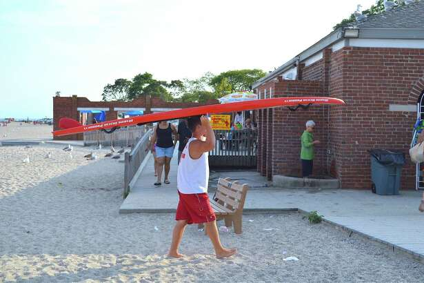 Lifeguard A.J. Hoffman puts away some of the key equipment at the end of the day at Compo Beach on Friday, Aug. 11, 2017, in Westport, Conn.
