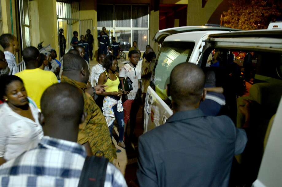 People evacuate the area where attackers opened fire on diners at a restaurant popular with foreigners in Ouagadougou, Burkina Faso, on Sunday night. Photo: AHMED OUOBA, AFP/Getty Images