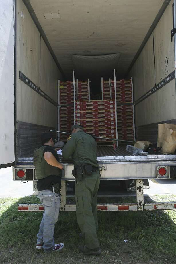 In this Aug. 13, 2017 photo, Border Patrol officers check the inside of a tractor-trailer in Edinburg, Texas. Police in Texas acting on a tip found the immigrants locked inside the tractor-trailer parked at a gas station about 20 miles (30 kilometers) from the border with Mexico, less than a month after 10 people died in the back of a hot truck with little ventilation in San Antonio. (Delcia Lopez/The Monitor via AP) Photo: Delcia Lopez, Associated Press