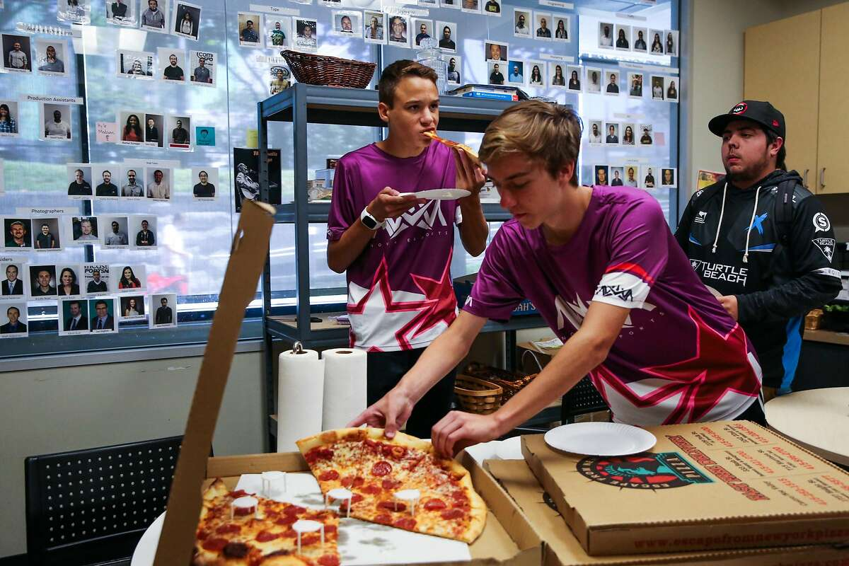 (l-r) Ellis Holdren (left) bites into a slice of pizza as Aidan Hannigan serves himself during a lunch break at a regional e-sports video game tournament at NBC studios in San Francisco, Calif., on Sunday, Aug. 13, 2017.