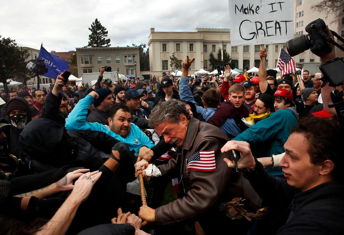 Tom Condon of San Francisco, center, a Trump supporter, becomes entangled in the center of a fight after attempting to push protesters back with his cane during a Pro-President Donald Trump rally and march at the Martin Luther King Jr. Civic Center park March 4, 2017 in Berkeley, Calif.