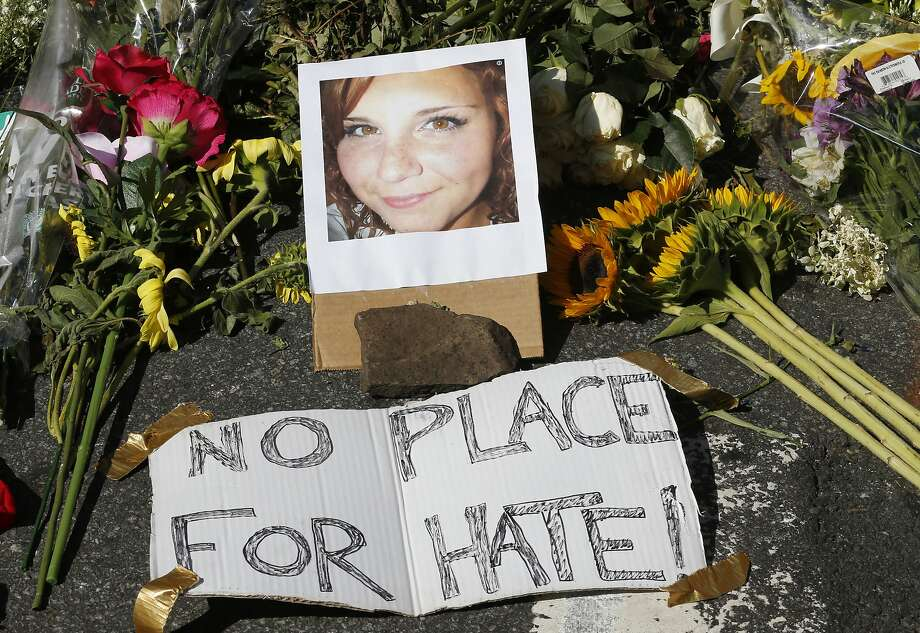 A makeshift memorial of flowers and a photo of victim, Heather Heyer, sits in Charlottesville, Va., Sunday, Aug. 13, 2017. Heyer died when a car rammed into a group of people who were protesting the presence of white supremacists who had gathered in the city for a rally. (AP Photo/Steve Helber) Photo: Steve Helber, Associated Press
