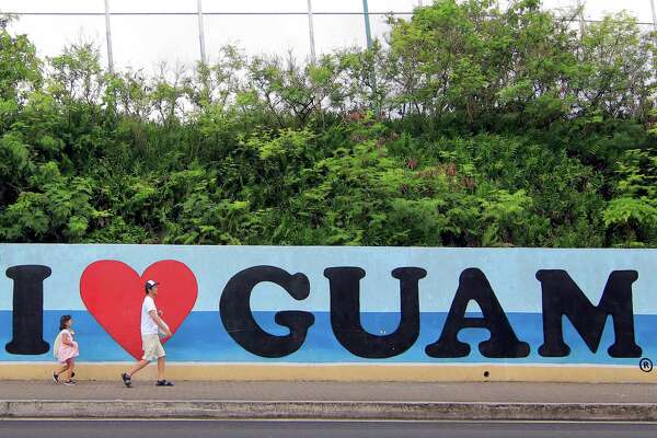 """Tourists walk past a wall painted with the slogan """"I love Guam"""" in the Tumon district on the island of Guam on Friday. Nuclear-armed North Korea announced a detailed plan on August 10 to send a salvo of four missiles over Japan and towards the US territory of Guam, raising the stakes in a stand-off with President Donald Trump and mocking him as """"bereft of reason."""" But Trump is also employing dangerous bluster in the matter."""