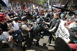 """White nationalists, neo-Nazis and members of the """"alt-right"""" clash with counter-protesters as they enter Lee Park during the """"Unite the Right"""" rally August 12, 2017 in Charlottesville, Virginia. After one person was killed and many more injured by a white supremacist who drove his car into a crowd of counter-protesters, President Donald Trump insisted that """"very fine people"""" were present at the rally. The Charlottesville rally is a symptom of how white nationalism has gained international traction, argues author Lawrence Rosenthal."""
