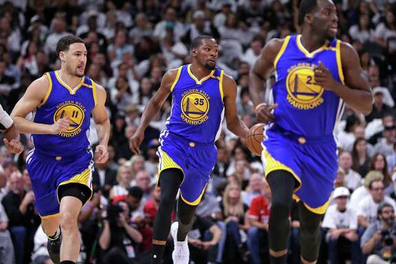 Golden State Warriors' Kevin Durant brings the ball up court flanked by Klay Thompson and Draymond Green in firsst quarter against the Spurs'during Game 3 of NBA Western Conference finals at AT&T Center in on May 20, 2017.