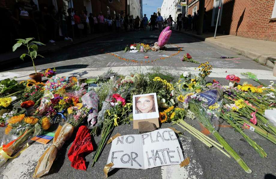 A makeshift memorial of flowers and a photo of victim, Heather Heyer, sits in Charlottesville, Va., Sunday, Aug. 13, 2017. Heyer died when a car rammed into a group of people who were protesting the presence of white supremacists who had gathered in the city for a rally. (AP Photo/Steve Helber) Photo: Steve Helber, STF / Copyright 2017 The Associated Press. All rights reserved.