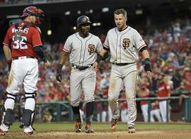 San Francisco Giants' Denard Span, center, helps Joe Panik, right, after he was tagged out at home by Washington Nationals catcher Matt Wieters (32) during the fourth inning of the second baseball game of a split doubleheader, Sunday, Aug. 13, 2017, in Washington. (AP Photo/Nick Wass)