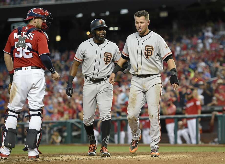San Francisco Giants' Denard Span, center, helps Joe Panik, right, after he was tagged out at home by Washington Nationals catcher Matt Wieters (32) during the fourth inning of the second baseball game of a split doubleheader, Sunday, Aug. 13, 2017, in Washington. (AP Photo/Nick Wass) Photo: Nick Wass, Associated Press
