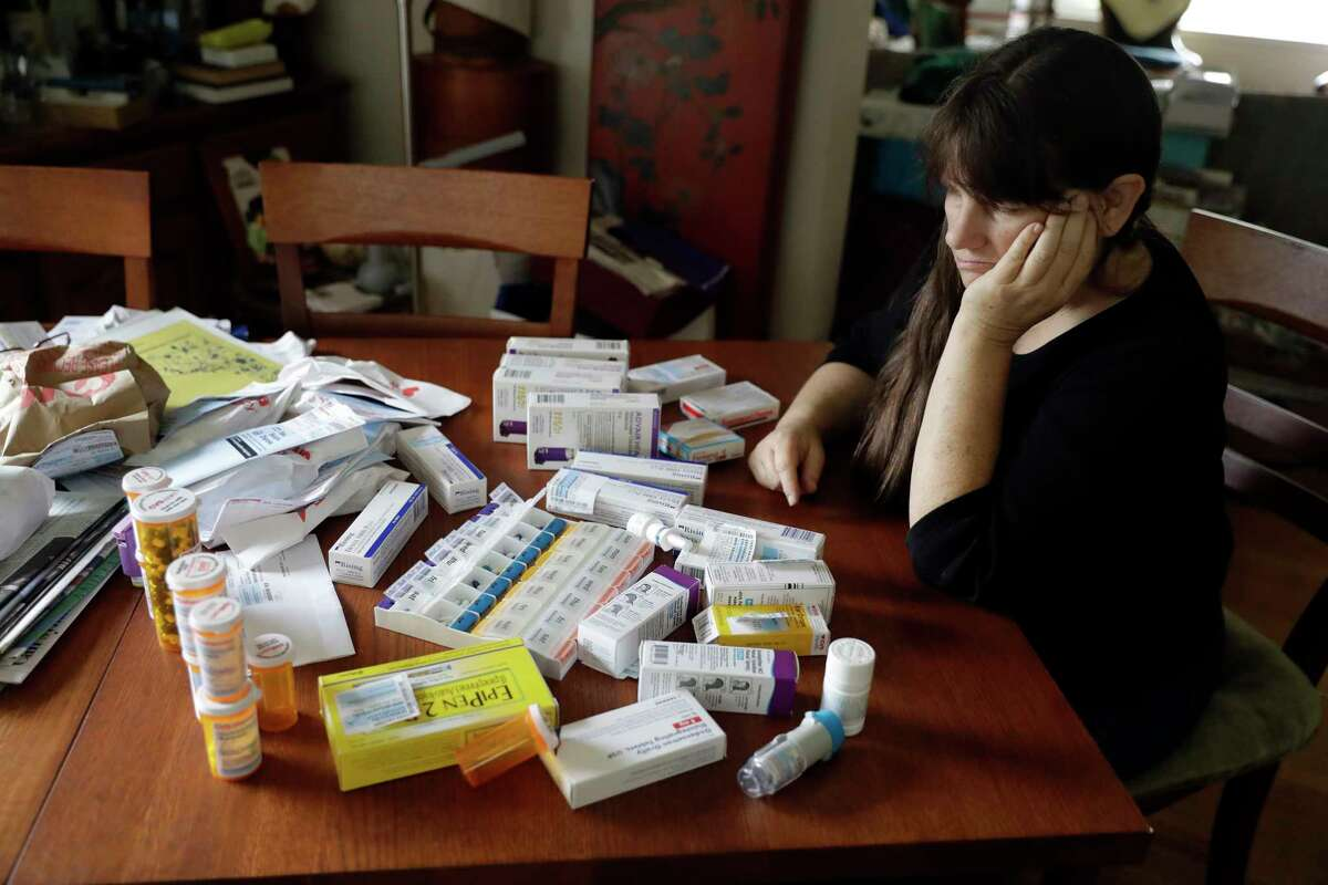 Sara Hayden looks at some of her medications at home Thursday, Aug. 10, 2017, in Half Moon Bay, Calif. Hayden lost her job as a data researcher because of medical problems and is now covered by Medi-Cal, as Medicaid is called in California. She has rheumatoid arthritis, and the medication she has to take to keep the disease in check cost thousands of dollars a month. The Medicaid program is a 1960s Great Society creation long criticized by conservatives. But it seems to have emerged even stronger after the Republican failure to pass health overhaul legislation. (AP Photo/Marcio Jose Sanchez)