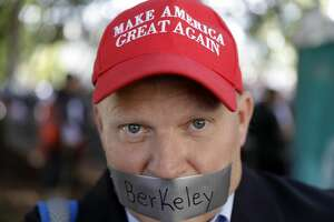 Daryl Tempesta tapes a sign over his mouth in protest during a demonstration Thursday, April 27, 2017, in Berkeley, Calif. Demonstrators gathered near the University of California, Berkeley campus amid a strong police presence and rallied to show support for free speech and condemn the views of Ann Coulter and her supporters. (AP Photo/Marcio Jose Sanchez)