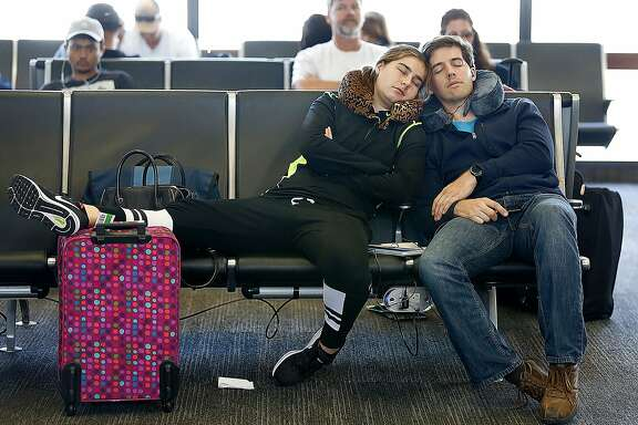 Passengers sleep while waiting for their flight at Terminal 3 of San Francisco International Airport on Thursday, July 20, 2017 in San Francisco, Calif.