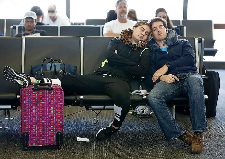 Passengers doze off while waiting for their flight at Terminal 3 of the San Francisco International Airport. Photo: Liz Hafalia, The Chronicle