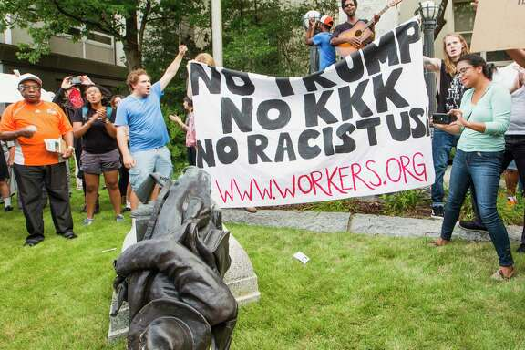 Protesters celebrate after toppling a statue of a Confederate solder in Durham, N.C. Monday, Aug. 14, 2017. Activists on Monday evening used a rope to pull down the monument outside a Durham courthouse. The Durham protest was in response to a white nationalist rally held in Charlottesville, Va., over the weekend. (Casey Toth/The News & Observer via AP)