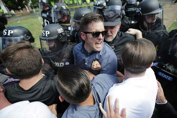 "CHARLOTTESVILLE, VA - AUGUST 12: White nationalist Richard Spencer (C) and his supporters clash with Virginia State Police in Lee Park after the ""United the Right"" rally was declared an unlawful gathering August 12, 2017 in Charlottesville, Virginia. Hundreds of white nationalists, neo-Nazis and members of the ""alt-right"" clashed with anti-facist protesters and police as they attempted to hold a rally in Lee Park, where a statue of Confederate General Robert E. Lee is slated to be removed."