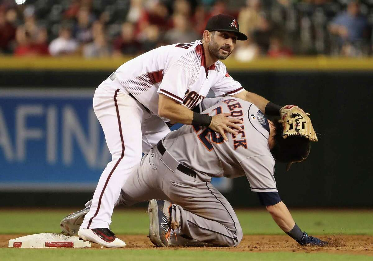 PHOENIX, AZ - AUGUST 14: Infielder Daniel Descalso #3 of the Arizona Diamondbacks falls onto Josh Reddick #22 of the Houston Astros after completing a double play during the sixth inning of the MLB game at Chase Field on August 14, 2017 in Phoenix, Arizona.
