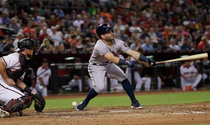 Houston Astros' Jose Altuve strikes out swinging as Arizona Diamondbacks catcher Jeff Mathis drops the ball during the third inning of an interleague baseball game, Monday, Aug. 14, 2017, in Phoenix. Altuve advanced to first safely on the dropped ball. (AP Photo/Matt York)