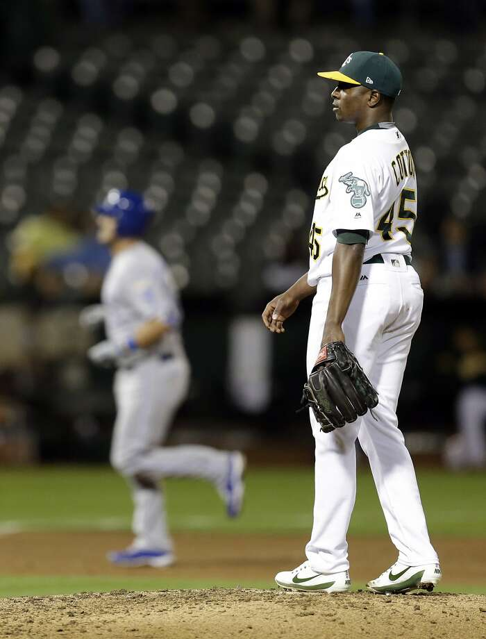 Oakland Athletics' Jharel Cotton, right, waits for Kansas City Royals' Cam Gallagher, left, to run the bases after hitting a grand slam in the sixth inning of a baseball game Monday, Aug. 14, 2017, in Oakland, Calif. Photo: Ben Margot, Associated Press