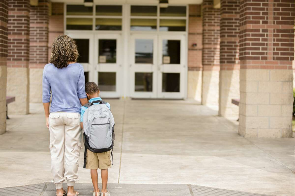 Little boy clings to his mom for reassurance on the first day of school.