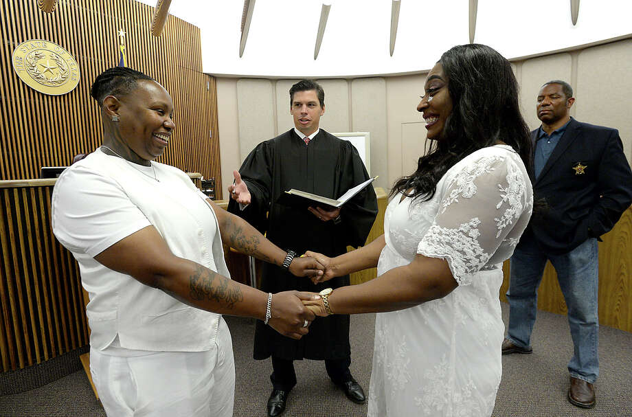 """Britney Taylor and Filisha Lilly react as Judge Baylor Wortham completes their. Wedding ceremony in his 136th district court Friday. Clerk Arthur Louis (at right) has jokingly dubbed the court """"the court of love,"""" as they have performed over 170 weddings so far this year. The number is an unprecedented spike in courthouse weddings, and the wall of photos from each is now spreading rapidly on a wall inside the judge's chambers. Photo taken Friday, August 11, 2017 Kim Brent/The Enterprise Photo: Kim Brent / BEN"""
