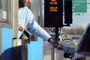 A New York State Thruway Authority toll collector collects the fee from a driver.