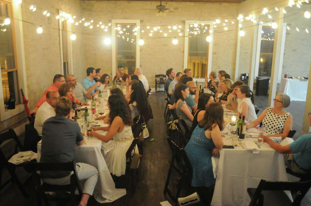 Saint City Supper Club participants enjoy a meal at a communal table at a past event.