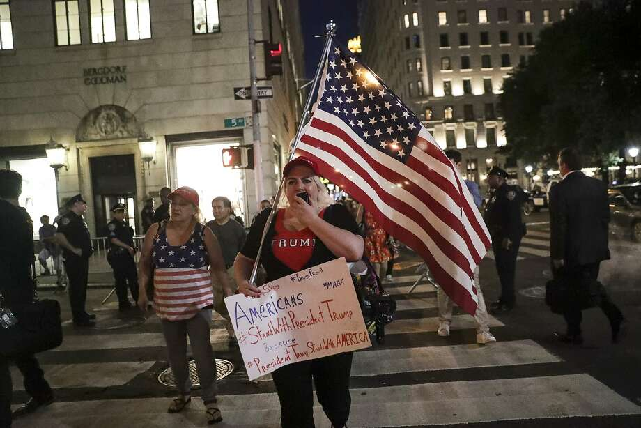 A supporter of President Trump holds an American flag and a sign during a rally outside of Trump Tower in New York on Monday. Photo: Jeenah Moon, Bloomberg