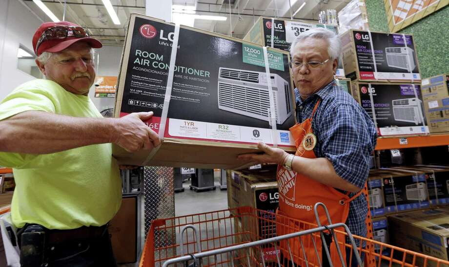 A store greeter (right) lends a hand to a customer to heft an air conditioning unit from a rapidly declining stock at a Home Depot store ahead of an expected heat wave in Seattle. On Tuesday, Home Depot's stock initially gained in early trading following the earnings results, then moved lower. In regular trading, it fell as much as 3.9 percent to $148.26. Photo: Elaine Thompson /Associated Press / Copyright 2017 The Associated Press. All rights reserved.