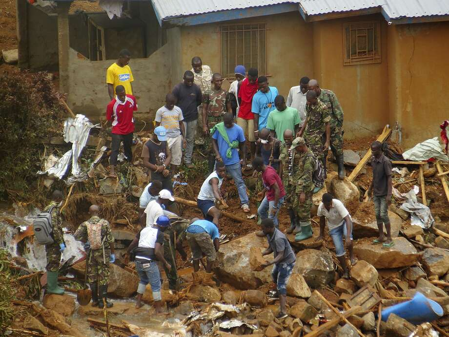 People search for bodies in the rubble after heavy rains caused flooding and mudslides in Freetown, Sierra Leone. Homes in the area were quickly buried or swept away in the deluge. Photo: Manika Kamara, Associated Press