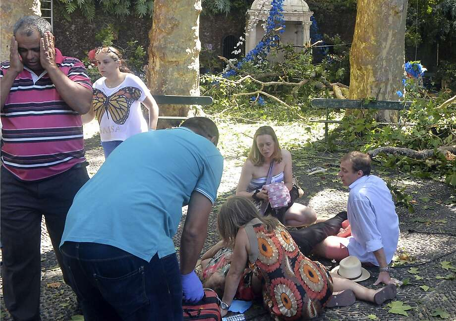 People help a person injured when a tree toppled at a religious gathering in Funchal, Portugal. Photo: ASPress, Associated Press